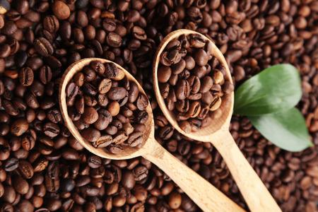 cafe colombiano: Granos de café con las hojas en una cuchara de madera