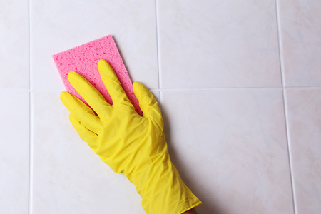 Cleaning kitchen tiles with sponge photo