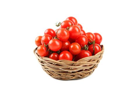 tomate cherry: Tomates de cereza en una cesta aislados en blanco Foto de archivo