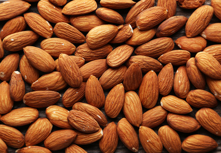 Almonds on brown wooden background photo