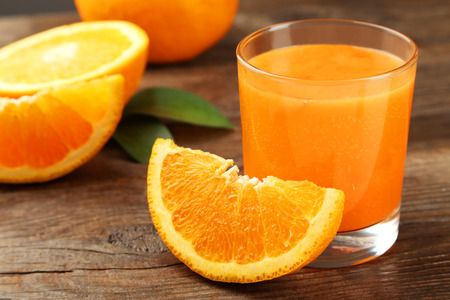 orange juice: Orange fruit and glass of juice on brown wooden background