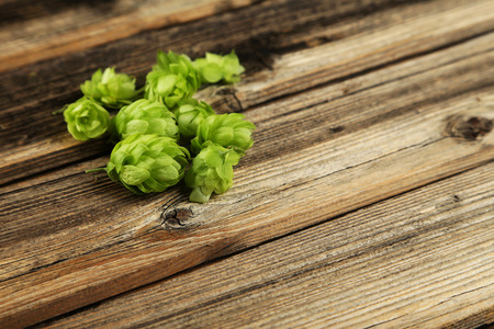 hops: Hops on brown wooden background Stock Photo