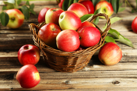 Apples in basket on brown wooden background
