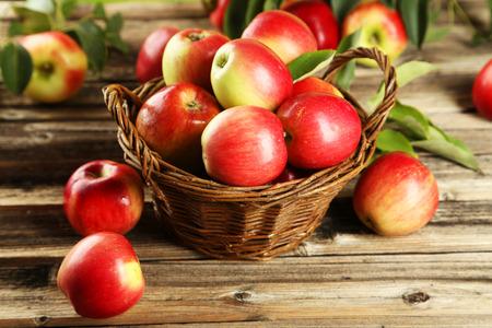 manzanas: Manzanas en la cesta sobre fondo de madera marrón