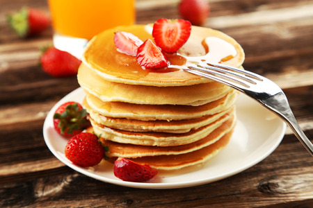 Delicious pancakes with strawberry on brown wooden background photo