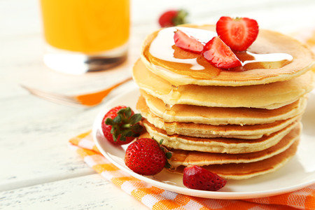 Delicious pancakes with strawberry on white wooden background photo