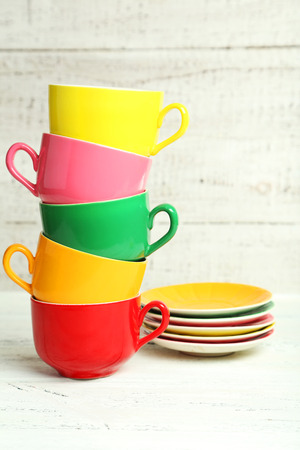 Colorful cups on white wooden background photo