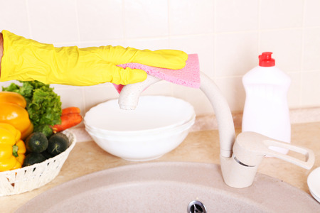 Male hand in gloves with sponge washing faucet photo