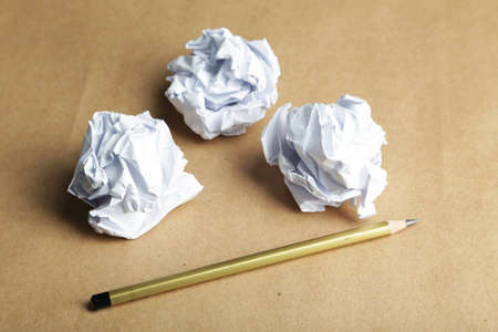 creasy: Crumpled paper balls with pencil on brown background Stock Photo