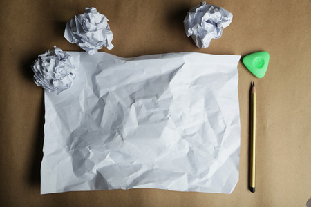 Crumpled up papers with a sheet of blank paper and a pencil on brown background photo