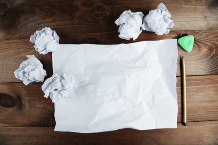 Crumpled up papers with a sheet of blank paper and a pencil on brown wooden background photo