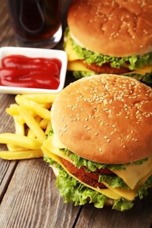 chicken burger: Big burgers on brown wooden background