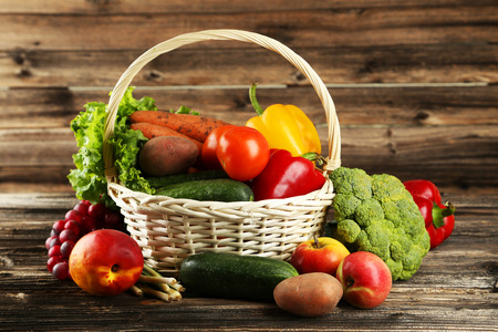 Vegetable in basket on brown wooden background photo