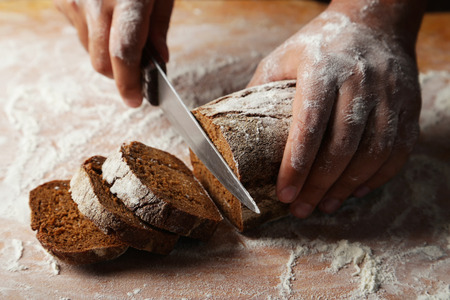 slicing: Male hands slicing fresh bread