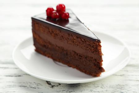 porcion de torta: Pastel de chocolate oscuro en el fondo de madera blanca