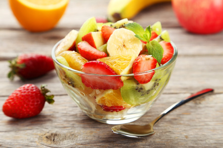 Fresh fruit salad in bowl on grey wooden background Stockfoto
