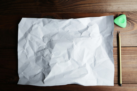 crinkle: Sheet of blank paper and a pencil on brown wooden background Stock Photo