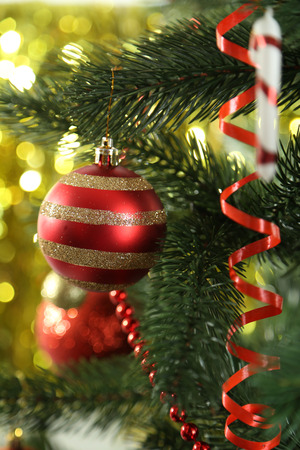 plastic christmas tree: Christmas baubles on christmas tree on lights background