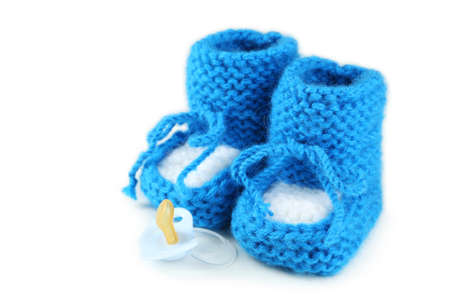 booties: Handmade baby booties with pacifier isolated on a white