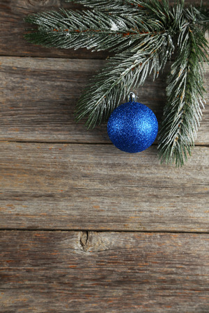 christmas ornamentation: Branch of Christmas tree with balls on grey wooden background Stock Photo