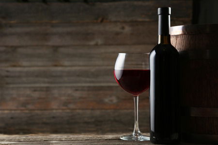 Red wine glass with bottle and barrel on grey wooden background Stockfoto