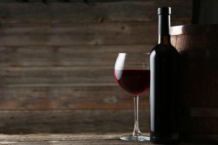 vino: Vidrio de vino rojo con la botella y el barril en el fondo de madera gris