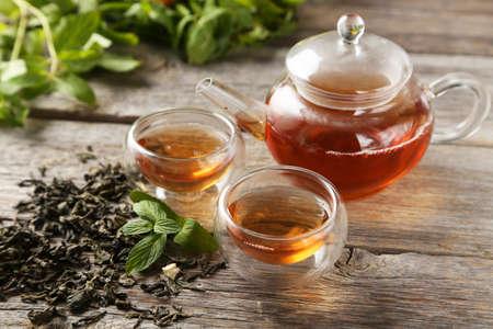 taza de te: Taza con t� verde y tetera sobre fondo de madera gris