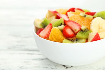 fruity salad: Fresh fruit salad on white wooden background