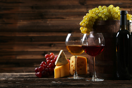 Glass of red and white wine, cheeses and grapes on brown wooden background Stock Photo