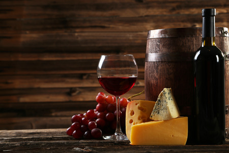 brown bottles: Glass of red wine, cheeses and grapes on brown wooden background Stock Photo