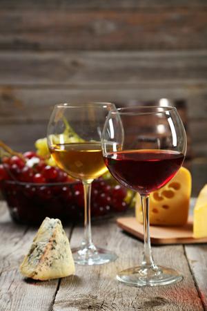 copa de vino: Vaso de vino tinto y blanco, quesos y uvas en el fondo de madera gris