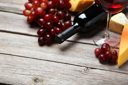 parmesan cheese: Glass of red wine, cheeses and grapes on grey wooden background