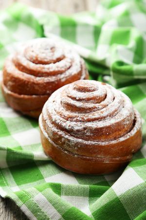 Freshly baked cinnamon buns on green napkin photo