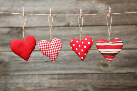 Love hearts hanging on rope on grey wooden background Фото со стока