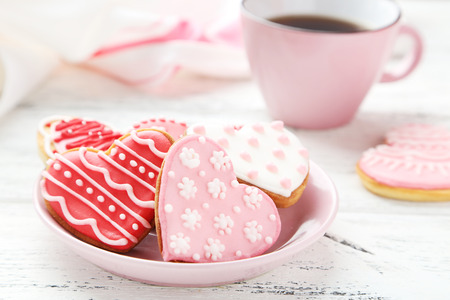 Heart cookies with cup of coffee on white wooden background photo