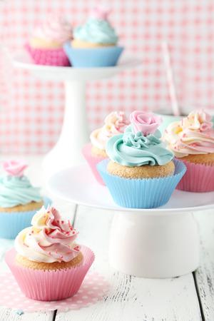 Tasty cupcake on white wooden background photo