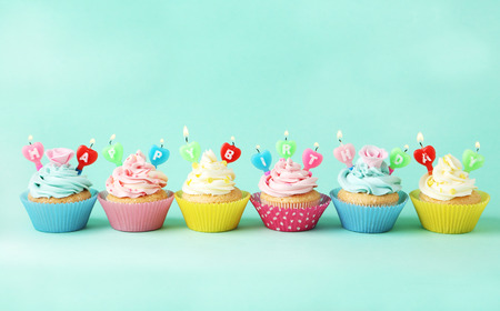 vanilla cupcake: Birthday cupcakes with candles on green background Stock Photo
