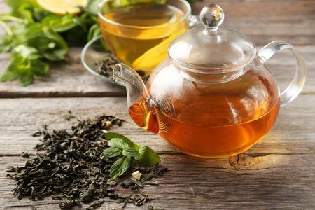 frutas secas: Taza con té verde y tetera sobre fondo de madera gris