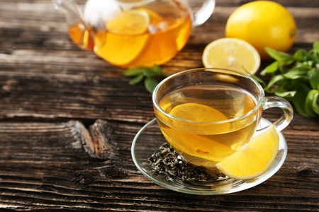 citron: Cup with green tea and teapot on brown wooden background