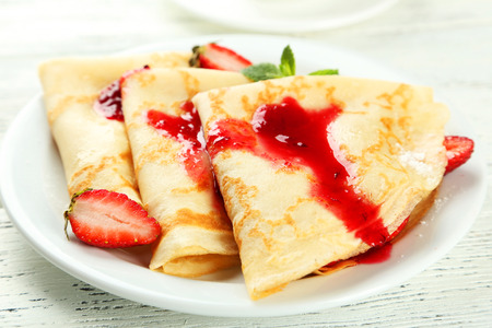 pancake: Pancakes with strawberry on plate on white wooden backgound