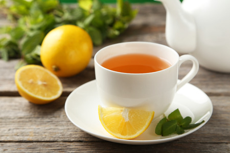 citron: Cup with green tea and teapot on grey wooden background Stock Photo