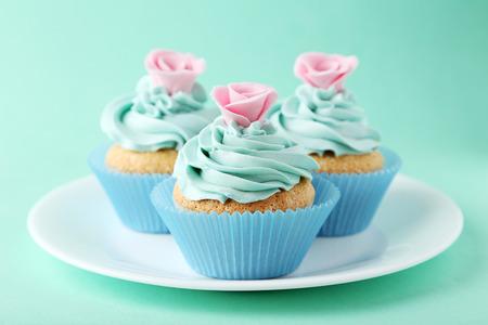 Geschmackvoller kleiner Kuchen auf Platte auf grünem Hintergrund