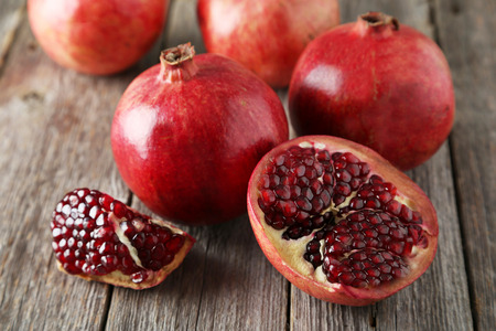 Delicious pomegranate fruit on grey wooden background Stock Photo