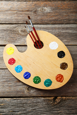 Wooden art palette with paints on grey wooden background photo