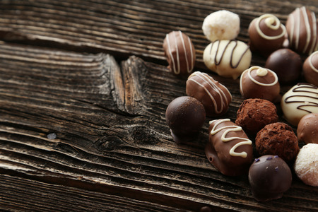 Chocolates on brown wooden background photo