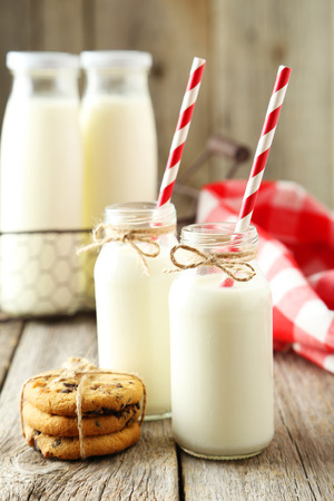 Two bottles of milk with striped straws on grey wooden background