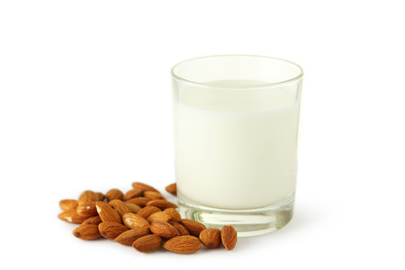 almond: Glass of milk with almonds isolated on white