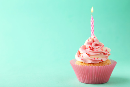 vanilla cupcake: Tasty cupcake with candle on green background