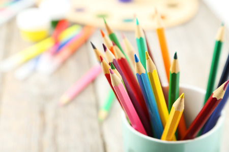 Colorful pencils in cup on grey wooden background