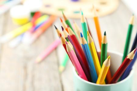 Kleurrijke potloden in kop op grijze houten achtergrond